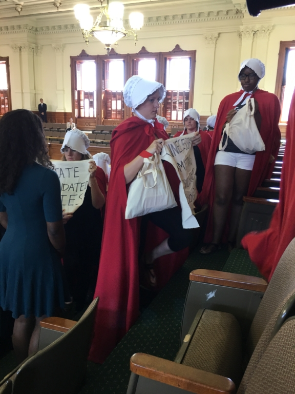 Women wearing red capes and white bonnets with handmade signs walking out of the gallery.