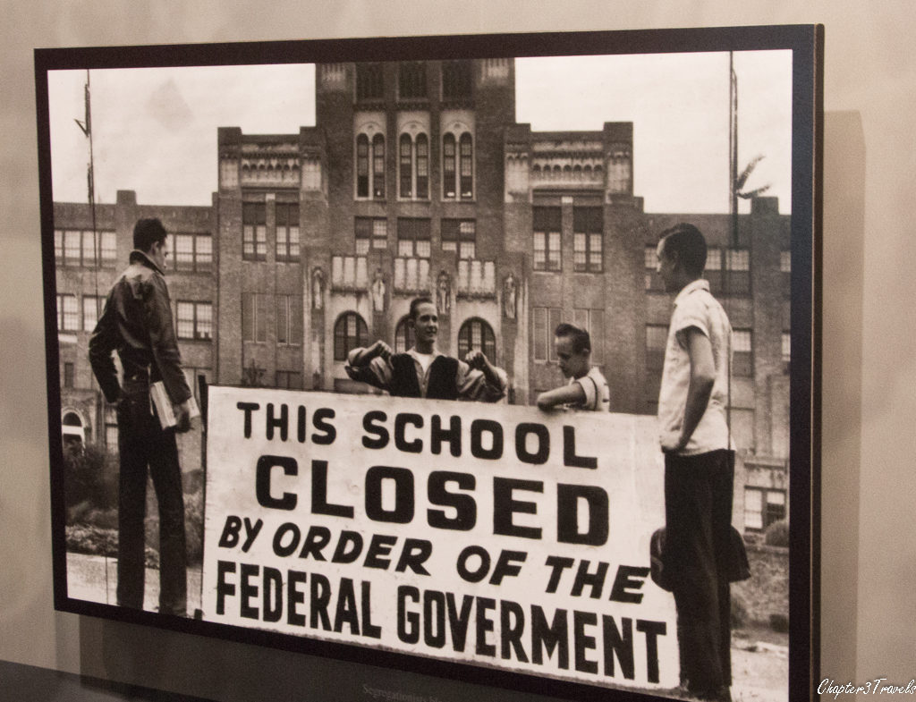 Photo of young men standing with sign in front of Central High School