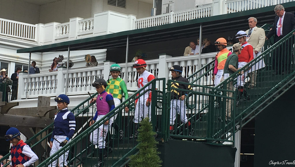 Eight jockeys walking down a staircase at Churchill Downs