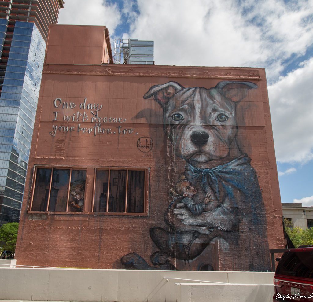 A large painting of a dog holding a child on the side of a building in Nashville, Tennessee.