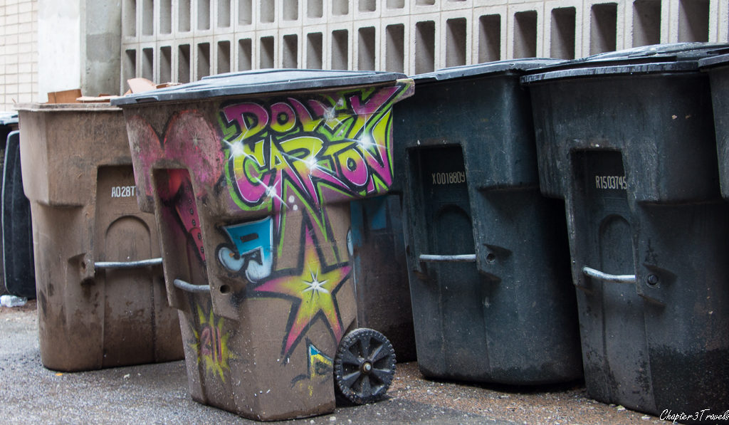 "A trashcan with the words ""Dolly Carton"" spray painted on the side."