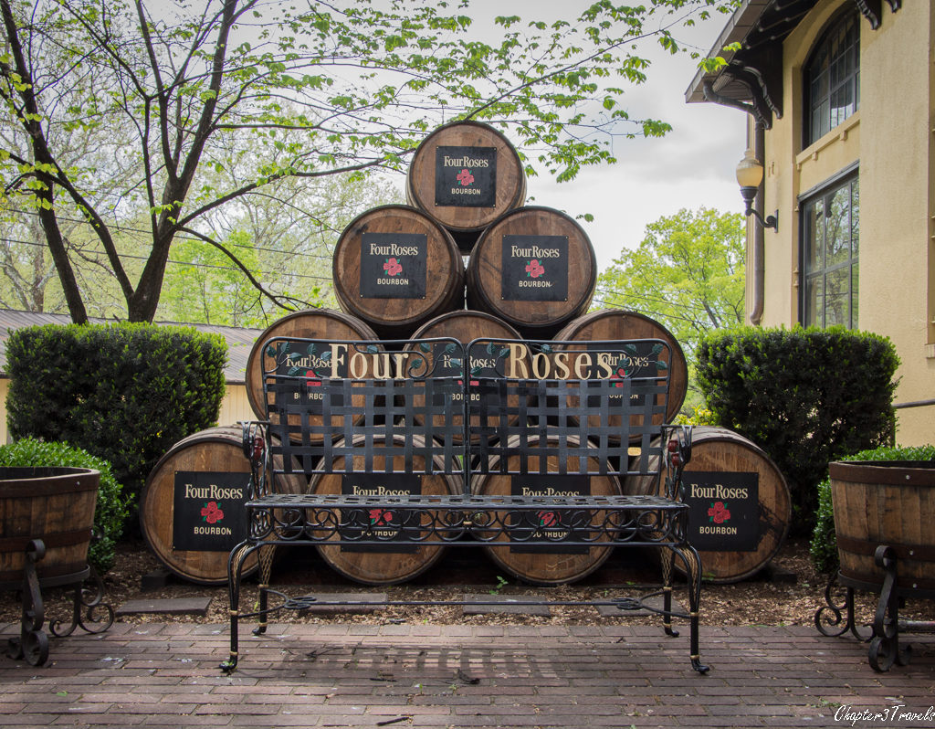 A bench in front of several stacked barrels at Four Roses Distillery