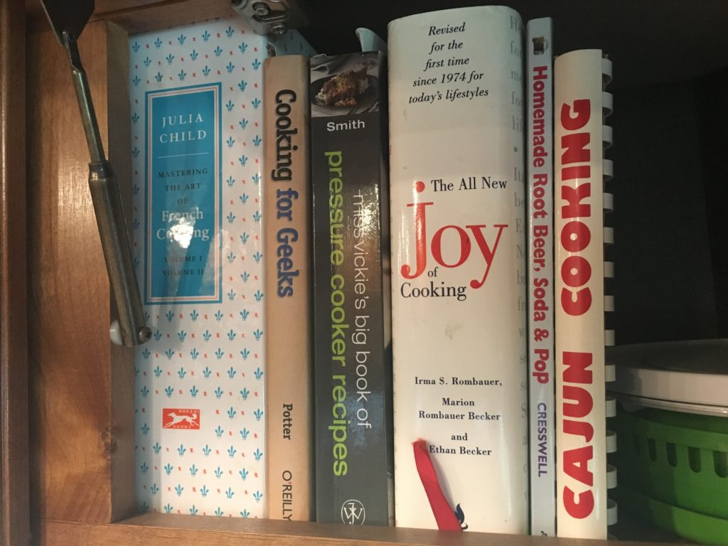 Cabinet shelf with cook books.