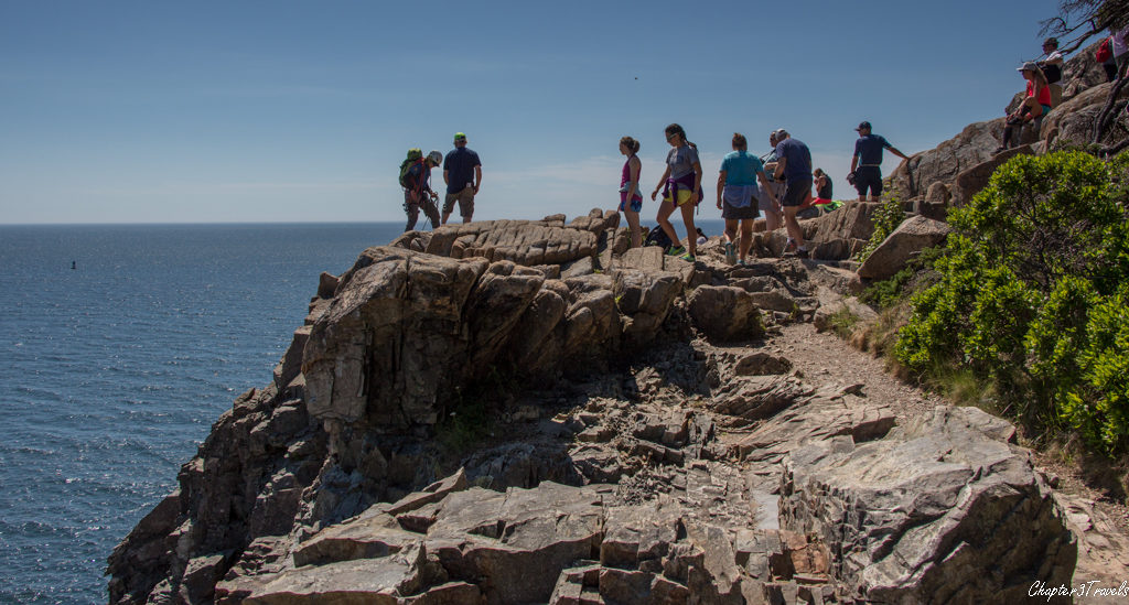 Visitors and a rock climber on top of Otter Cliffs at Acadia National Park