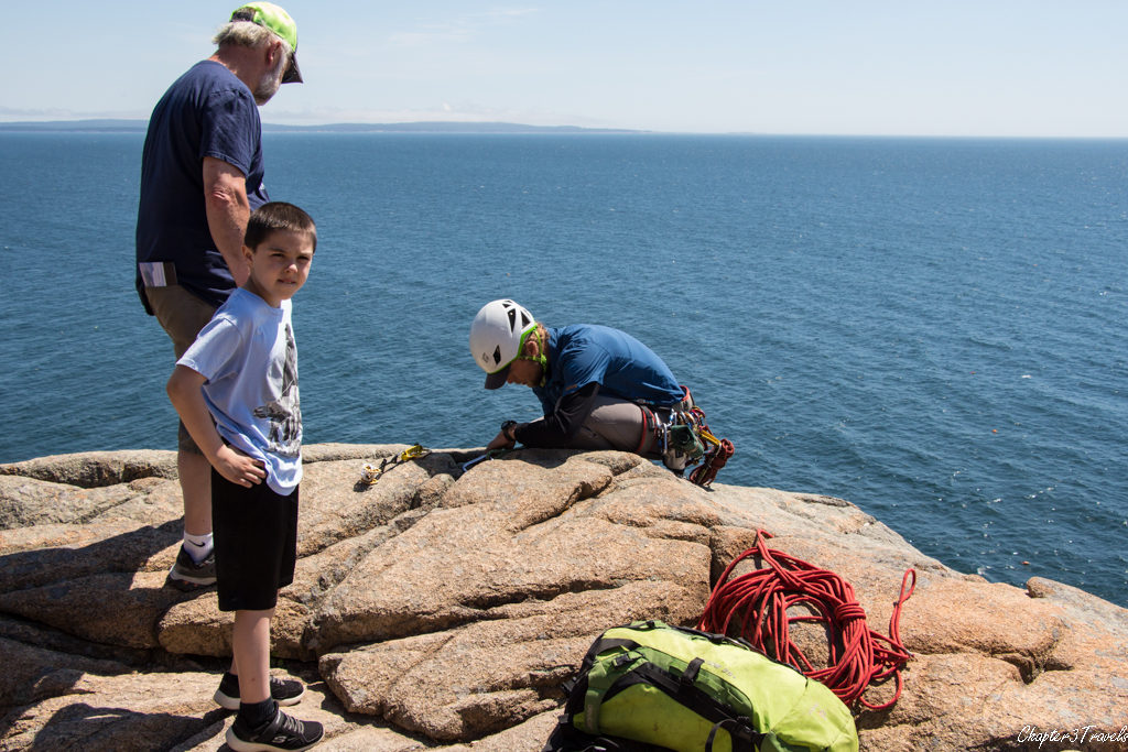 Tourist talking to rock climber on top of Otter Cliffs