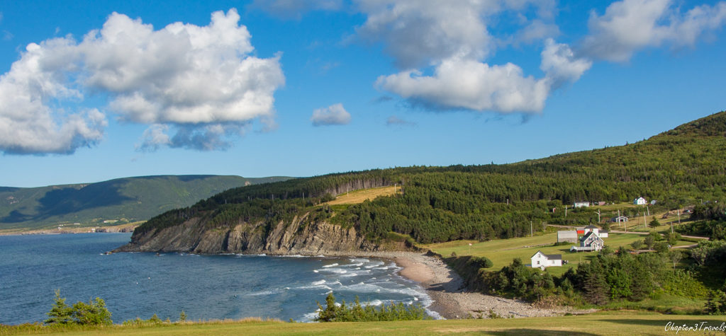 Homes on a hill overlooking the ocean with cliffs in the back on Cape Breton Island