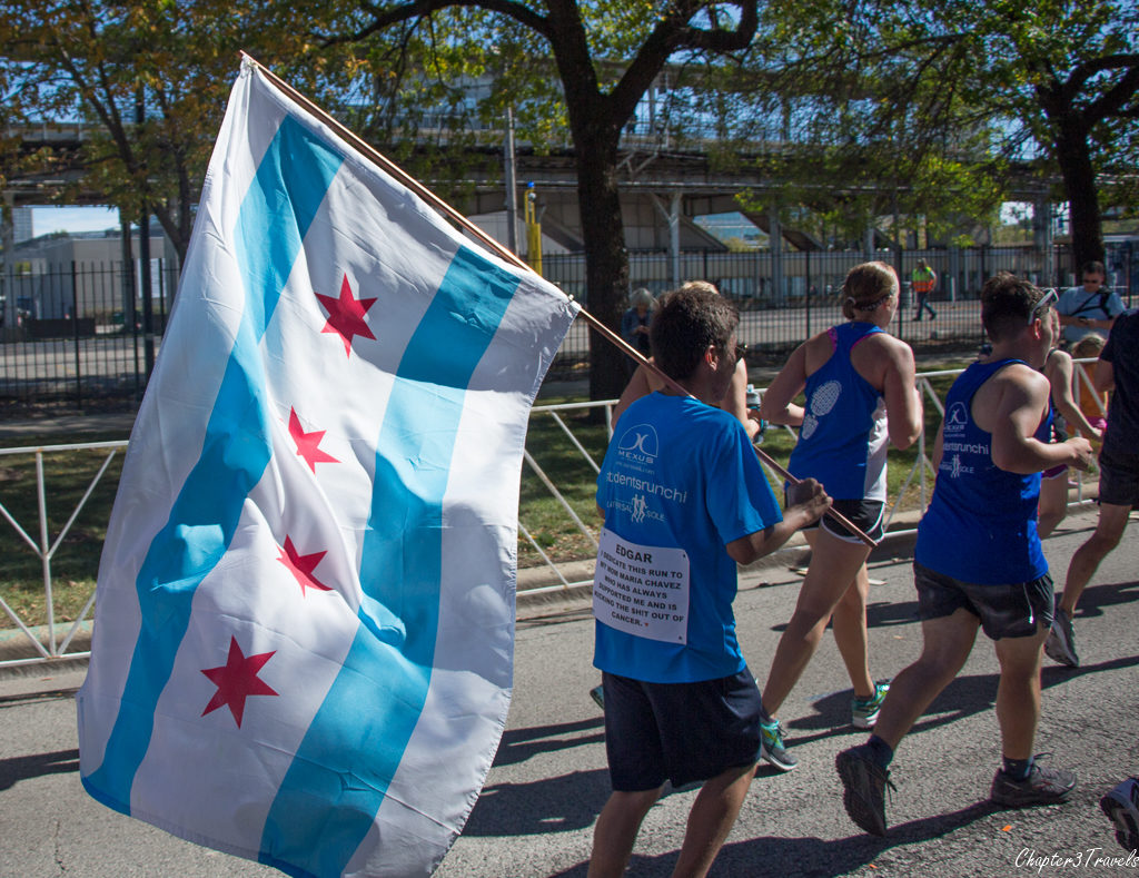 Runner carrying flag with sign on his shirt at the 2017 Chicago Marathon