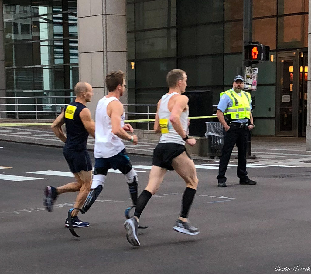 A runner with prosthetic legs running next to two guides at the Chicago Marathon