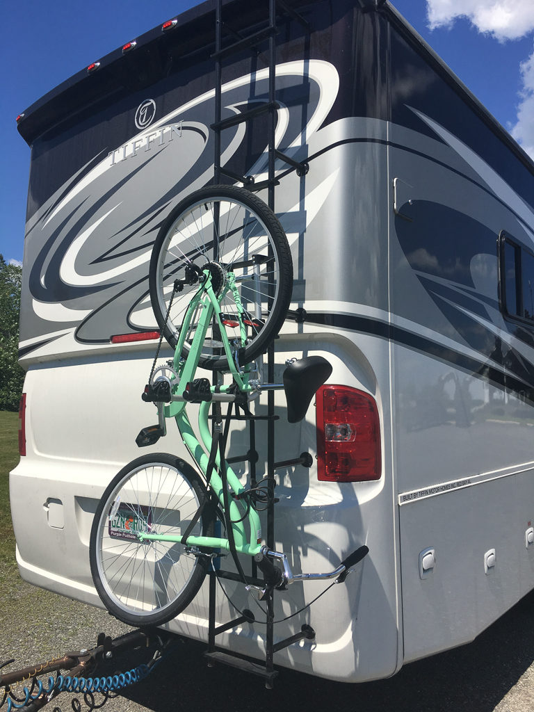 Bicycle hanging from ladder attached to motorhome