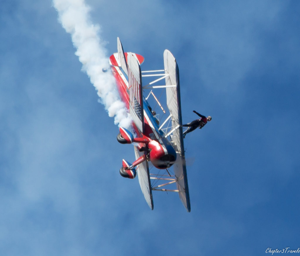 Wing walker standing on top of plane while plane is angled toward the ground