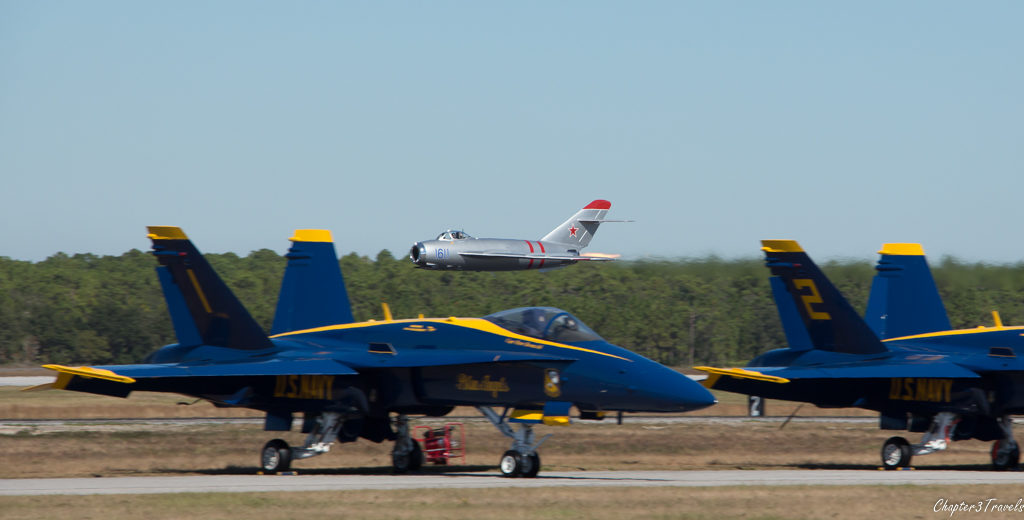 Mig flying low behind Blue Angel jets parked on the runway