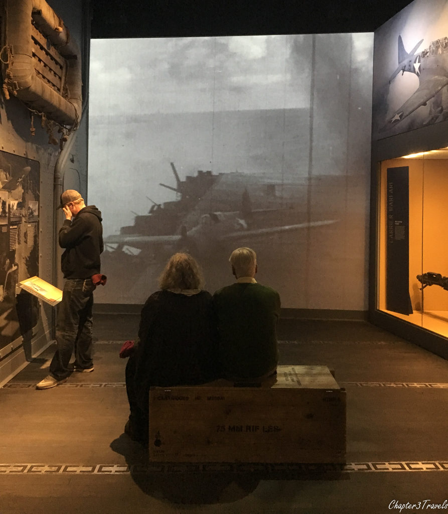 A couple watches a video about aircraft carrier landings during the war