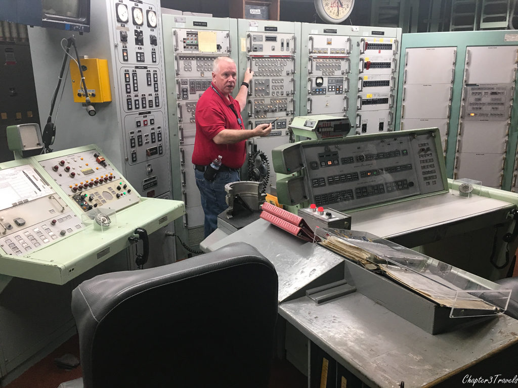 Tour guide pointing to butterfly valve lock in command and control room at Titan Missile Museum