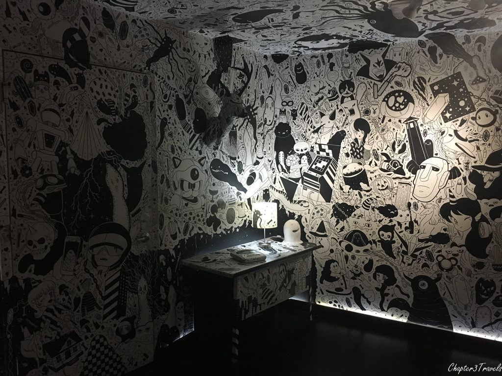 Room covered in black and white drawings at meow Wolf