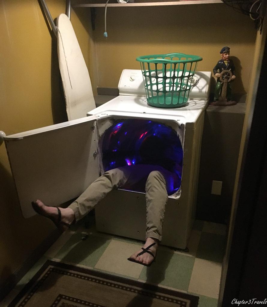 Man climbing into secret passageway through washing machine