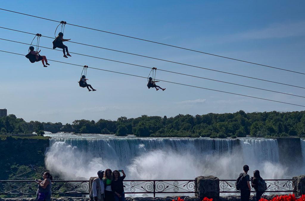 People ziplining in front of Niagara Falls