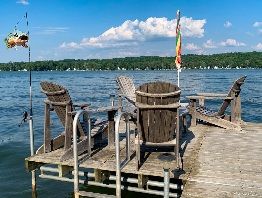 Adirondack chairs on pier over lake