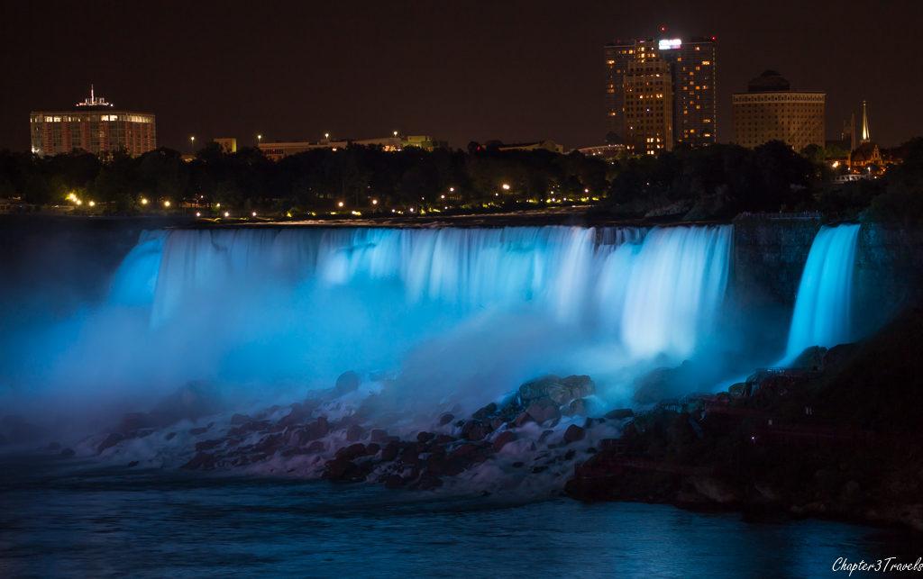 Niagara Falls lit up at night in blue