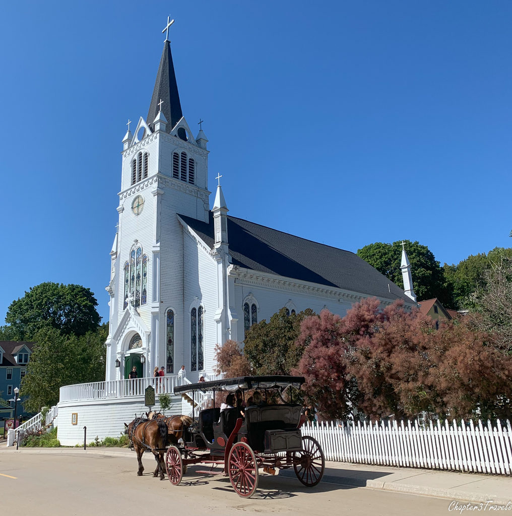 Horse drawn carriage in front of a historic church on Mackinac Island