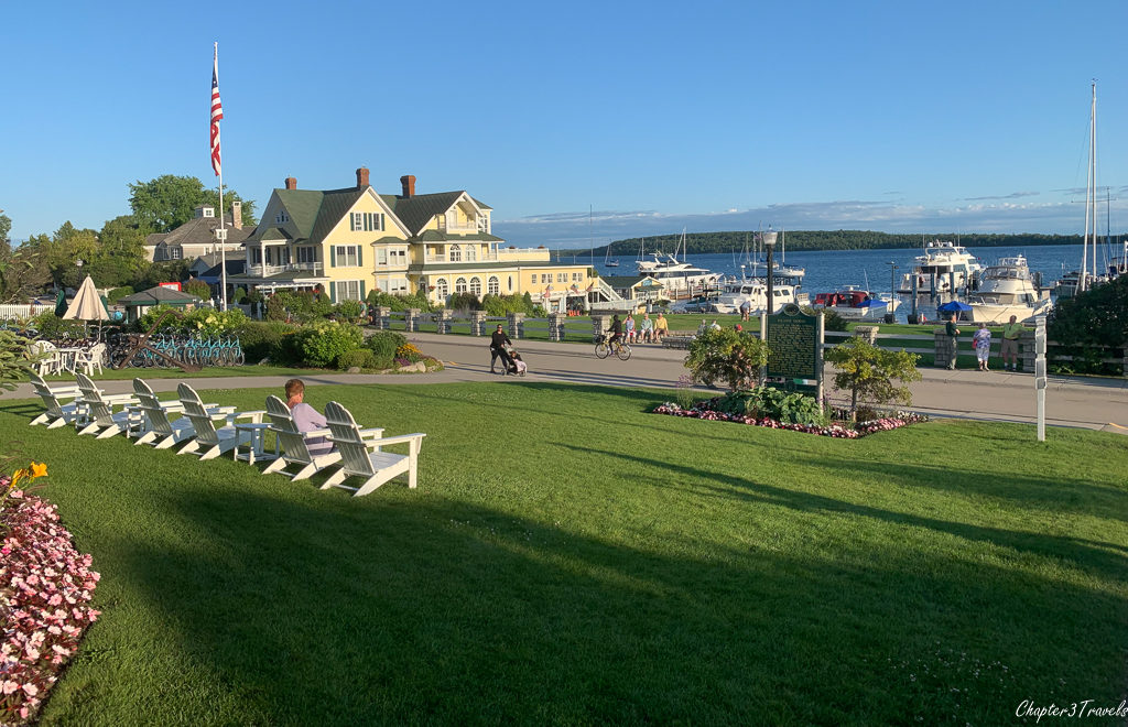 Adirondack chairs on lawn facing lake on Mackinac Island