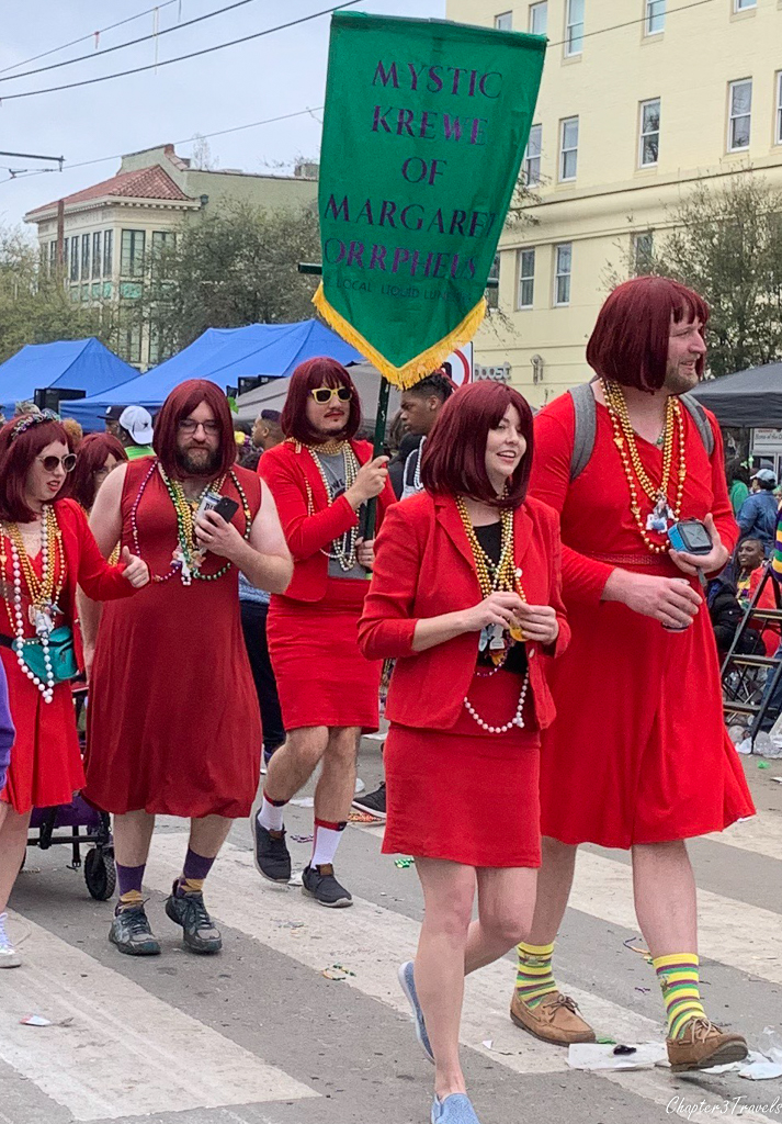 Men and women in matching red dresses and red wigs at Mardi Gras