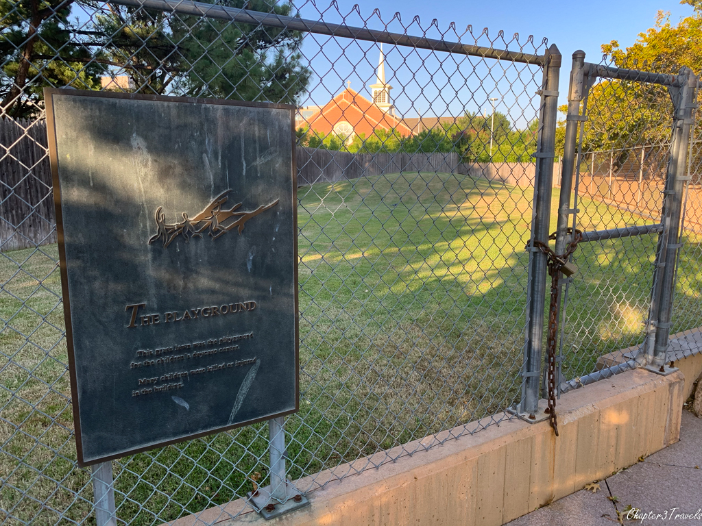 Fenced off grassy area where playground was