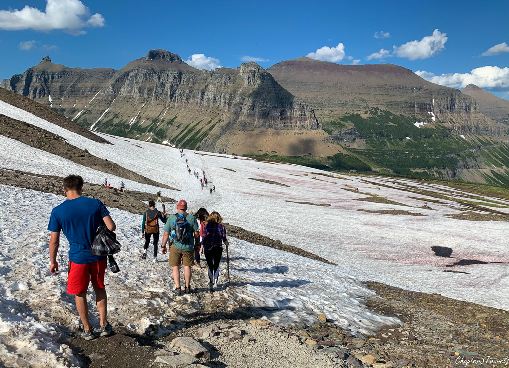 Hikers crossing snow fields at Hidden Lake Trail in Glacier National Park