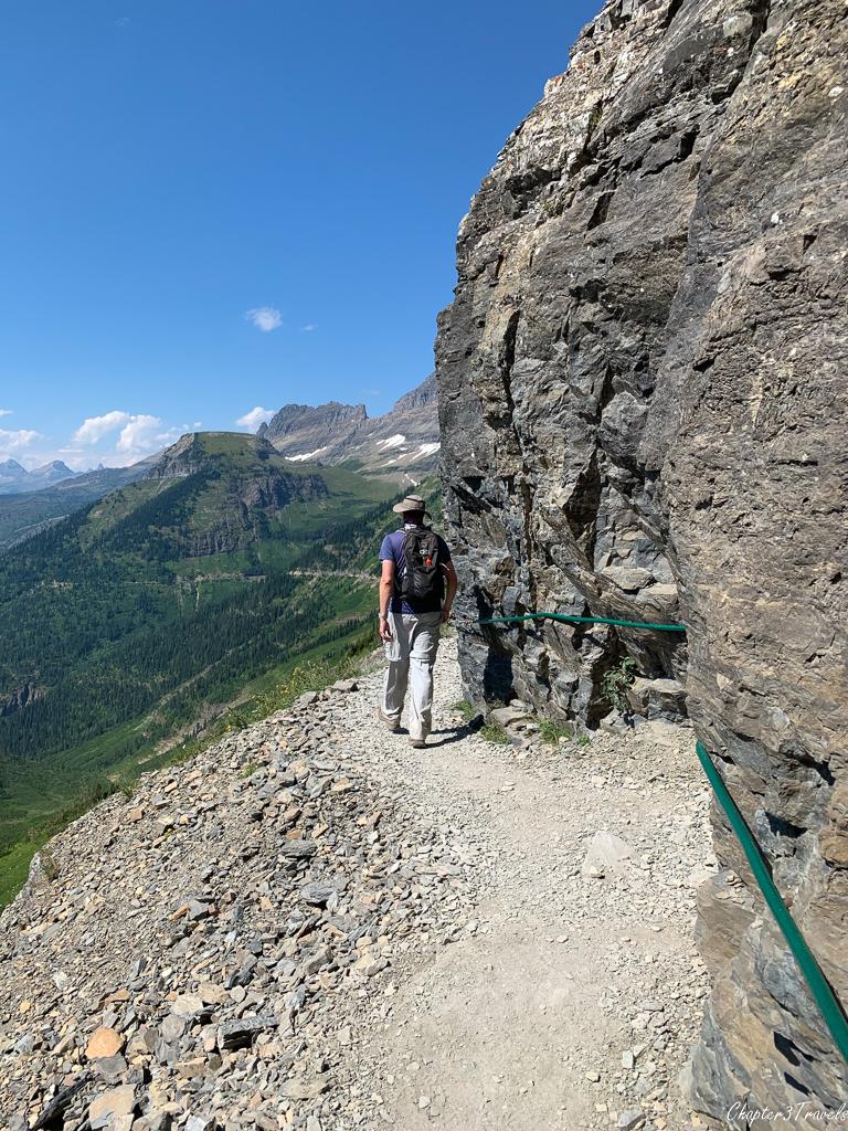 Kevin walking along cliff side trail on Highline Trail at Glacier National Park