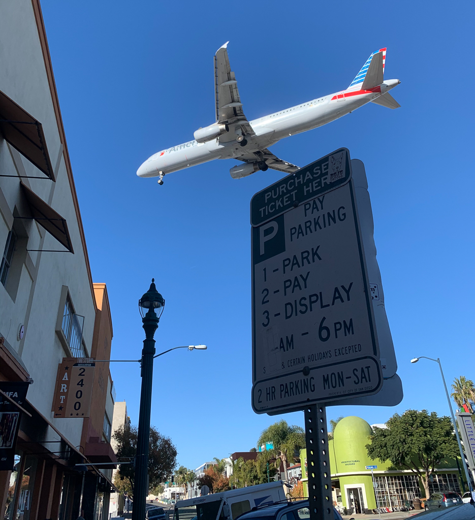 Plane flying over street sign in Little Italy