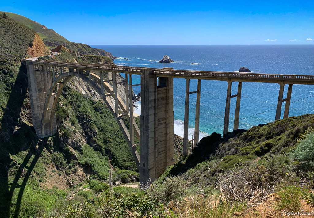 Backside view of arched bridge in front of ocean