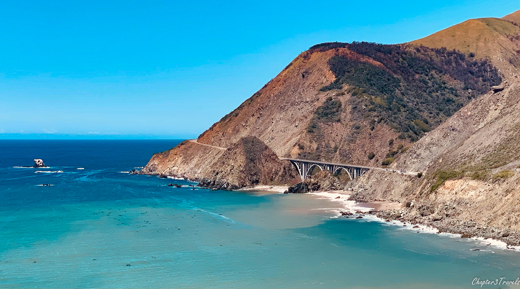 Bridge spanning river inlet into turquoise ocean