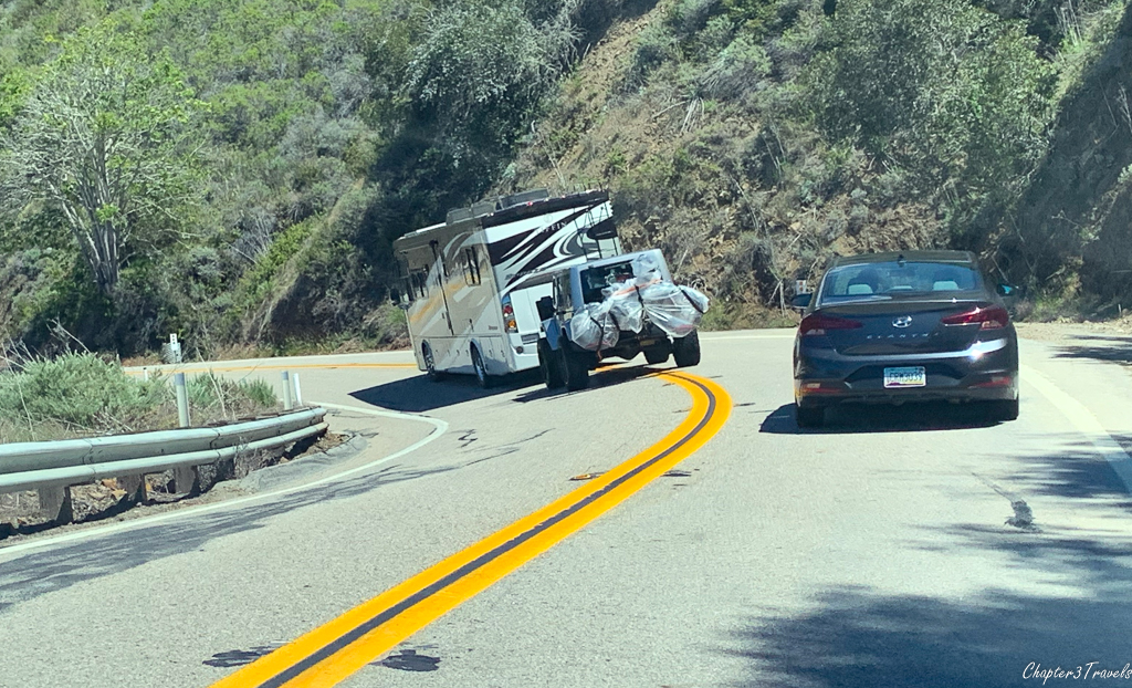 Motorhome with tow car driving in middle of curving road, across center line.