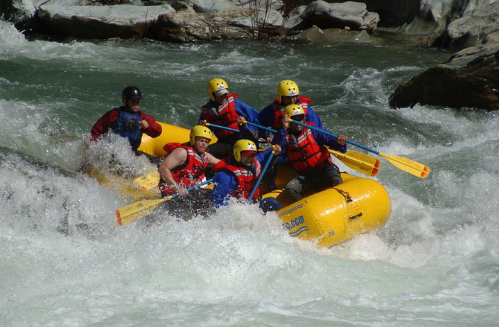 six people in raft paddling whitewater