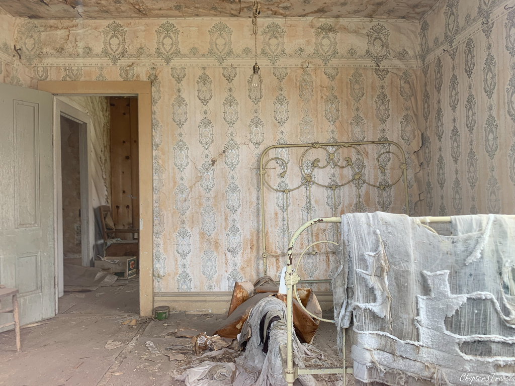 Interior of bedroom in Bodie. Stained walls, peeling wall paper, and decayed bedding on bed frame