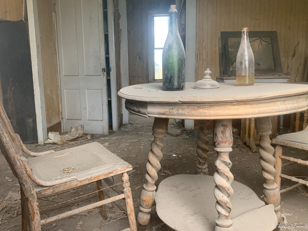 Dust covered table and chairs inside dilapidated home in Bodie