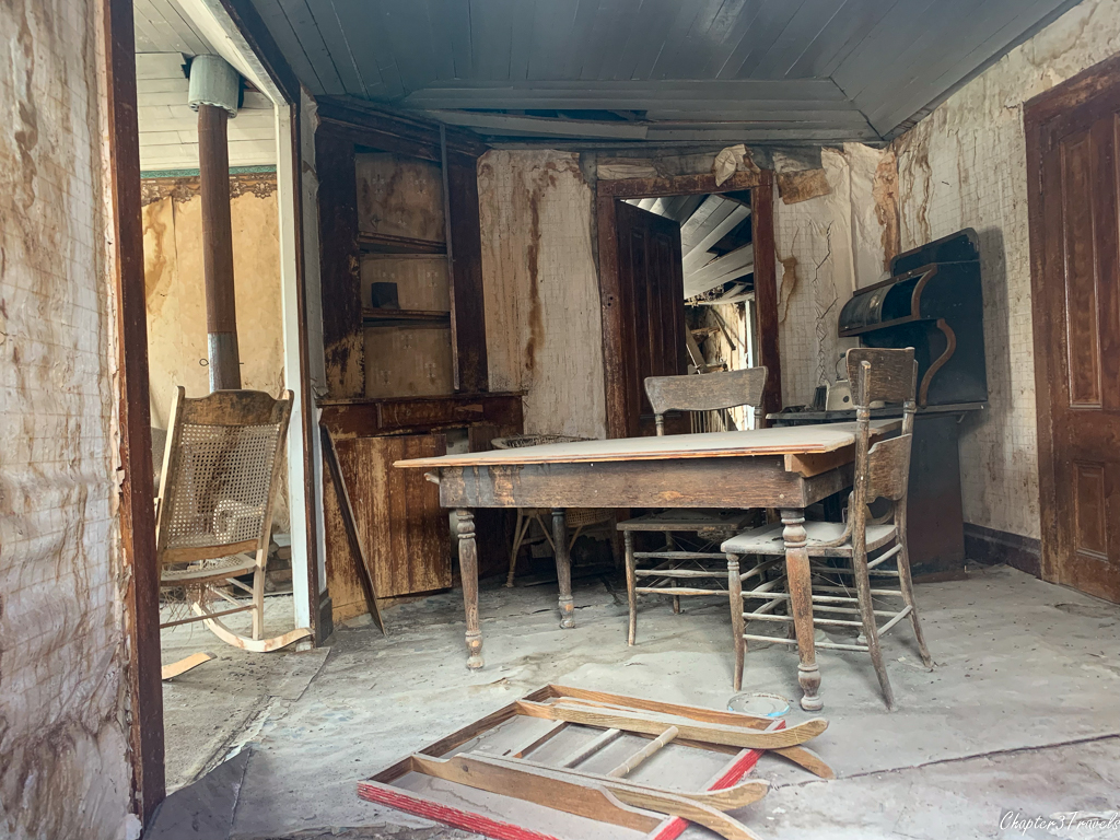 Tables, chairs, and empty bookcase in dilapidated Bodie house