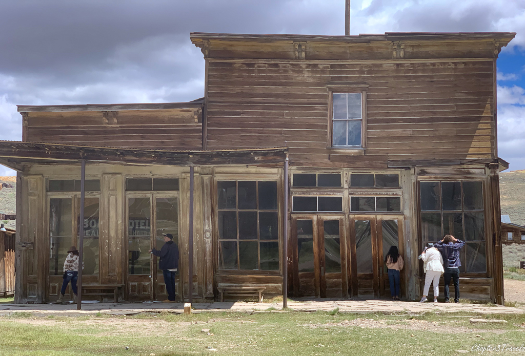 Tourists peering into the windows of a building in Bodie State Historic Park