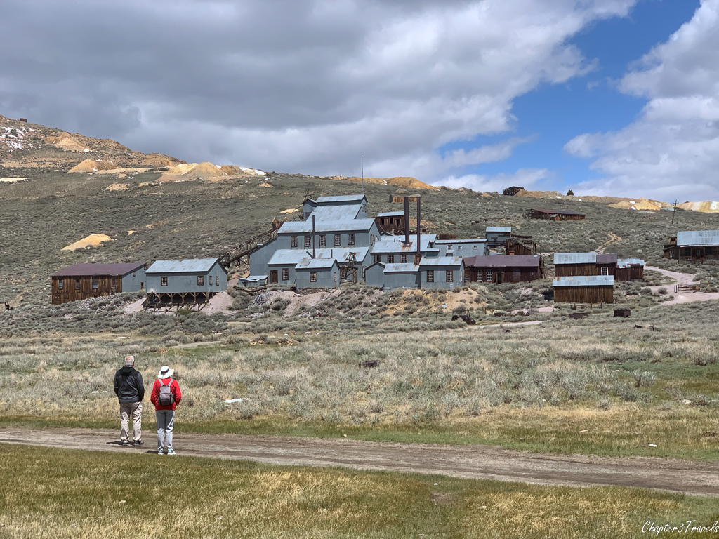 Two visitors looking up at the Bodie stamp mill