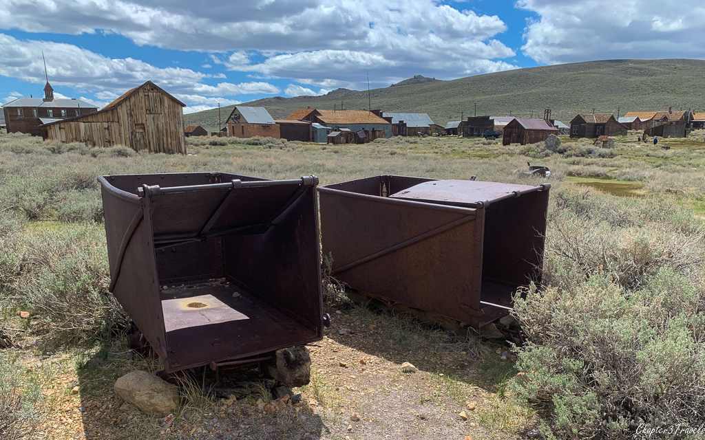 Rusted mining carts sitting in a field