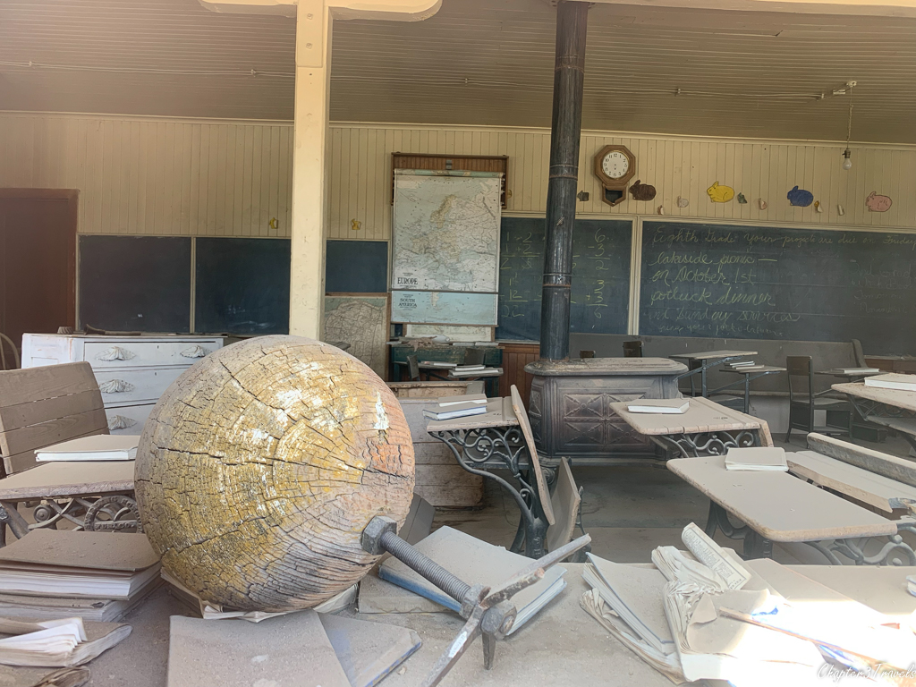 Interior of Bodie's schoolroom with dust covered desks and chairs as well as cracked and faded globe
